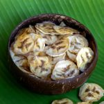 Bananes séchées au déshydrateur dans un bol en coco et sur une feuille de bananier.