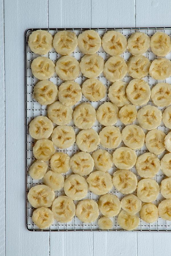 Rondelles de bananes sur une grille avant séchage au déshydrateur.